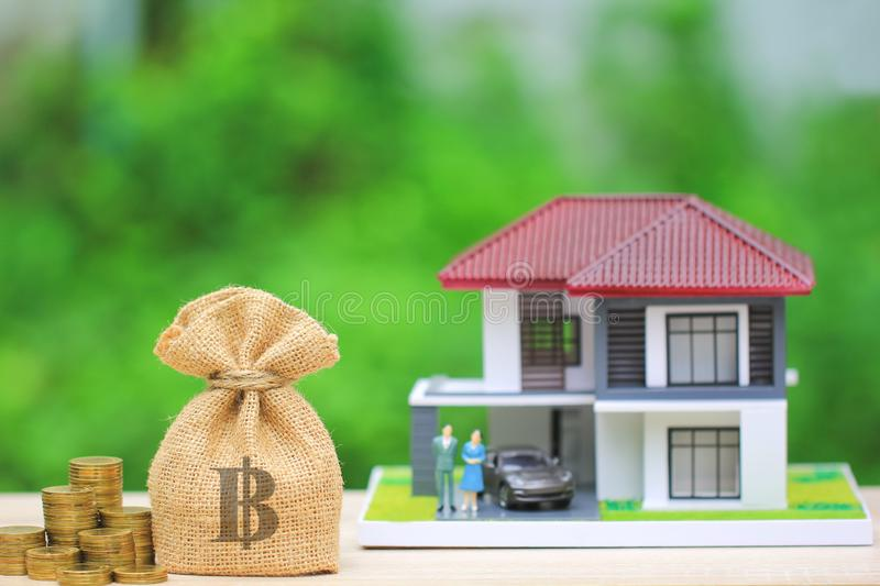Stack of gold coins money and bag with model house on natural green background, Investment and Real estate concept.  royalty free stock photo