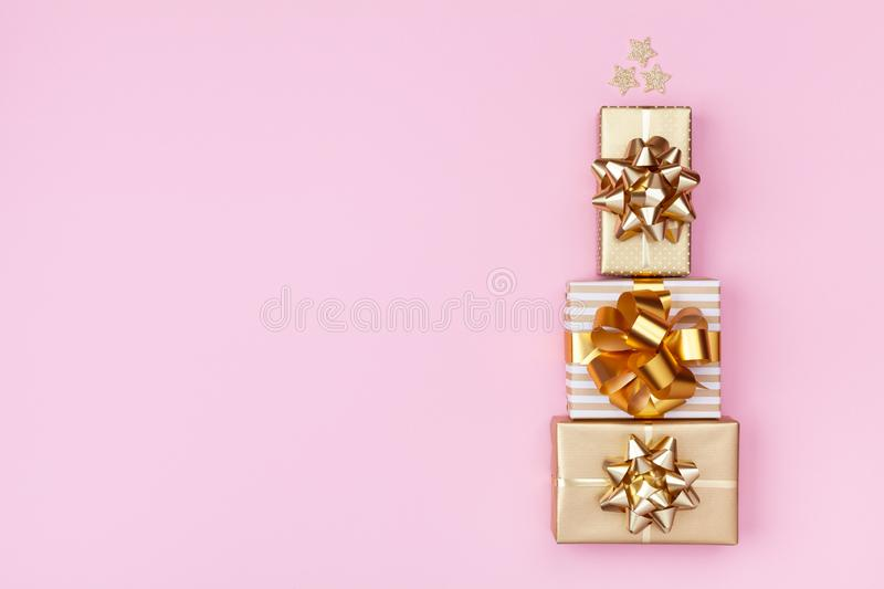Stack of golden gift or present boxes in the form of Christmas tree on pink top view. Celebration Christmas or New year. Flat lay royalty free stock photography