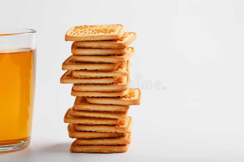 A stack of golden wheat cookies and a mug of fragrant green tea in on a white background. Cookies laid out in a breakfast column stock photography