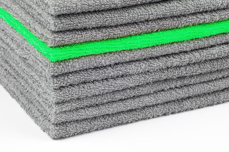 Stack of gray and green terry towels, conceptual background. Close-up stock photos
