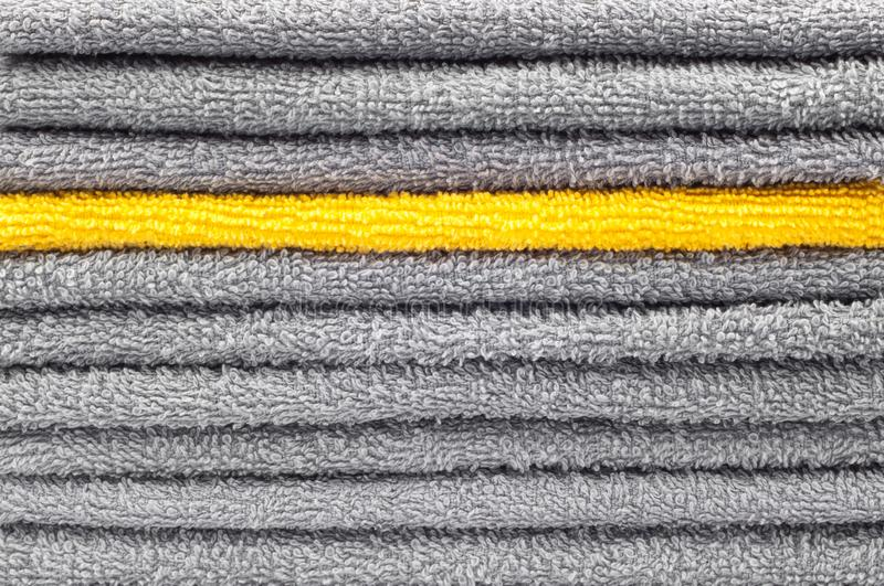 Stack of gray and yellow terry towels, conceptual background. Close-up stock image