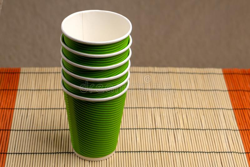 A stack of green paper cups on a bamboo stand.  stock photo