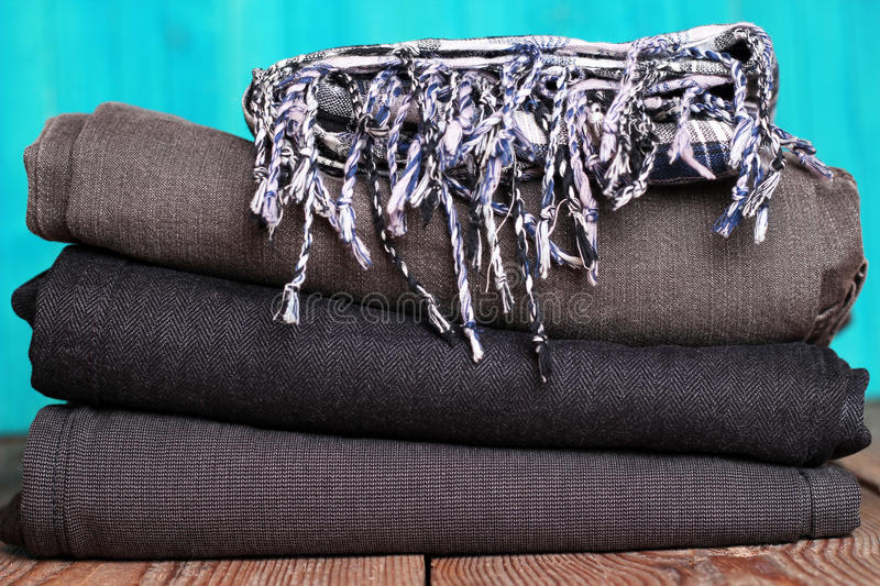 Stack of grey and black blue jeans with scarf on a wooden table. With bright turquoise background stock images