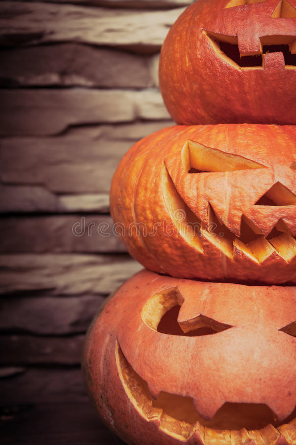 Stack of halloween jack o lanterns in vertical orientation on blurred stone background royalty free stock images