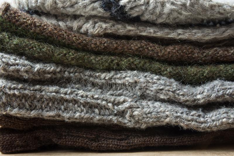 Stack of Handmade Warm Knitted Socks Scarfs Mittens From Rough Wool Yarn Brown Beige Grey. Close up. Winter Autumn Eco Fashion stock images