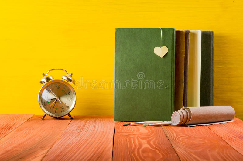 Stack of hardback books, diary on wooden deck table and yellow background. Back to school. Copy Space. Education stock photos