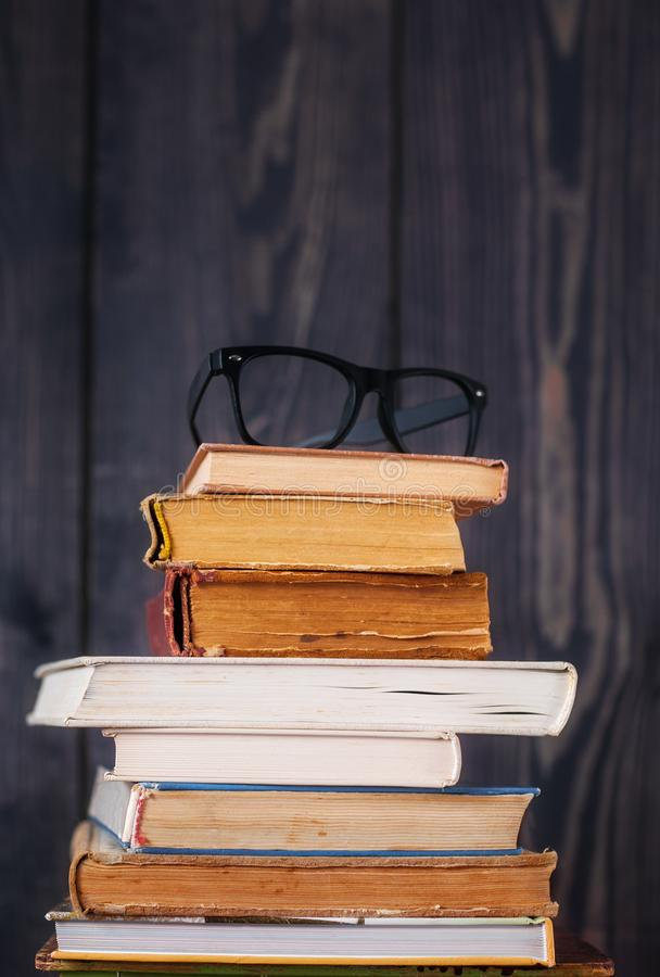 Stack of hardback books with reading glasses on dark wooden background. Back to school. Copy space stock photos