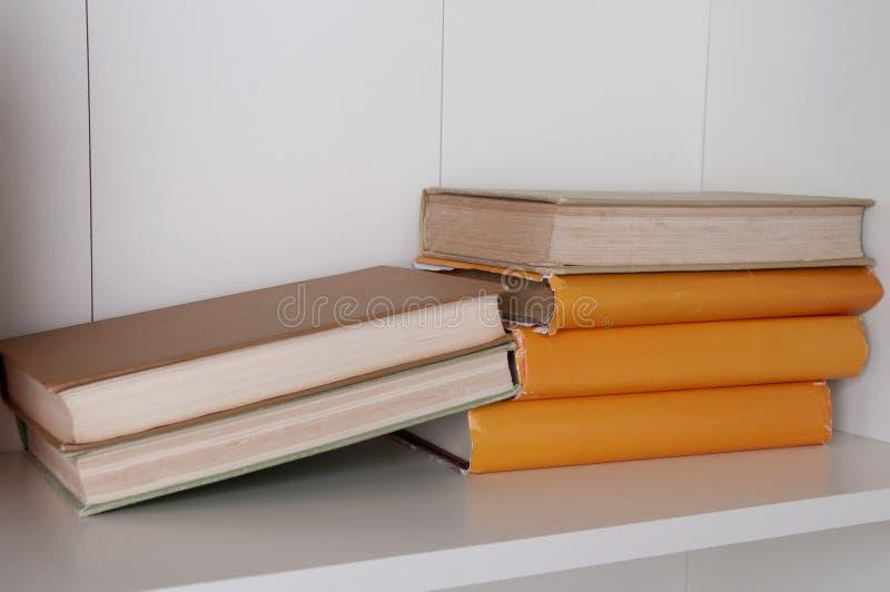 Stack of hardback books on wooden bookshelf. royalty free stock images