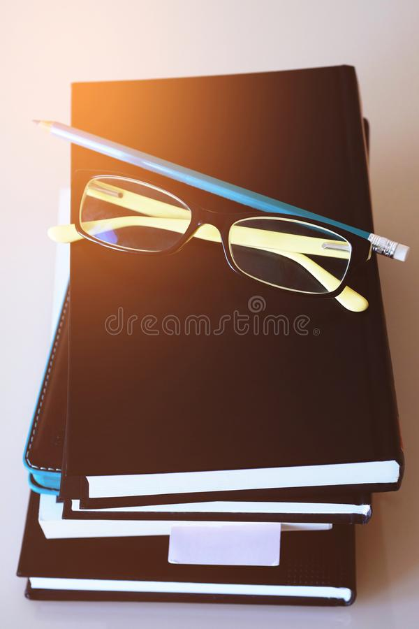 A stack of hardcover books and notebooks on a white background, glasses and a pencil on a stack of books. Office concept royalty free stock images
