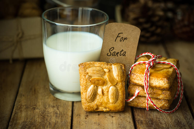 Stack of homemade almond Christmas cookies tied with red and white ribbon, glass of milk, note with written words for santa. Clause, rustic style, festive stock photos