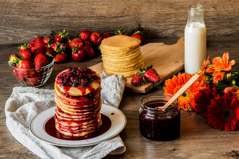 Stack of homemade american pancakes served with jam and strawberries on wooden background royalty free stock photography