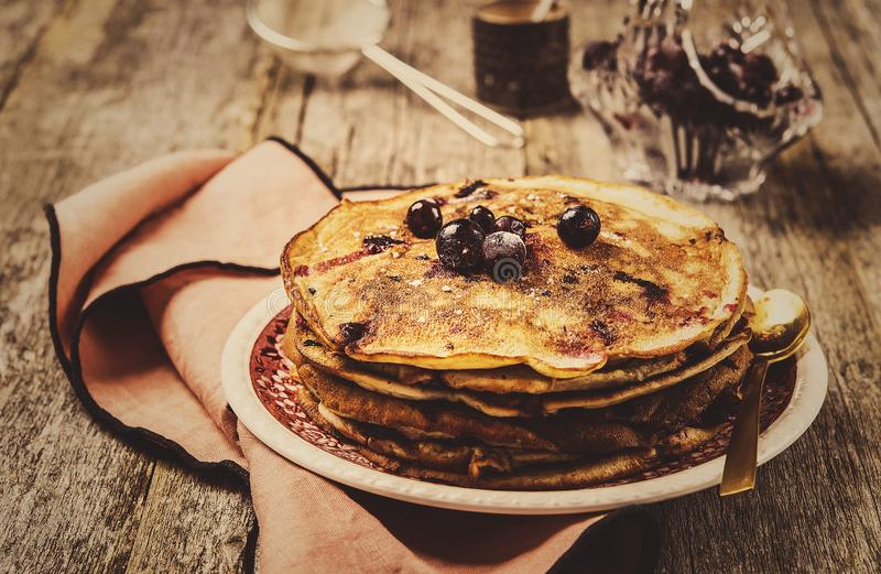 Stack of homemade freshly baked pancakes crepes with black currant berries. On a rustic vintage wooden background. Healthy breakfast. Selective focus. Toned stock photography