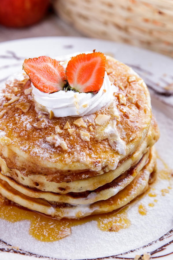 Stack of homemade pancake with maple syrup and strawberry topping. Close up portrait of stack of homemade pancake with maple syrup and strawberry topping royalty free stock photo