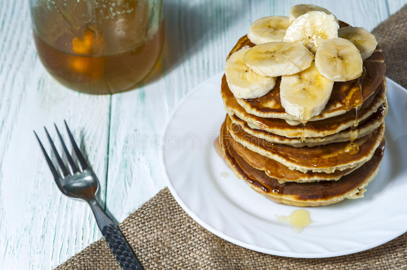 Stack of homemade pancakes with banana slices and honey on white plate with fork and linen napkin on wooden background. Russian holiday pancake week.Horizontal stock photography