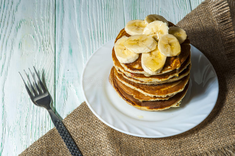 Stack of homemade pancakes with banana slices and honey on white plate with fork and linen napkin on wooden background. royalty free stock images
