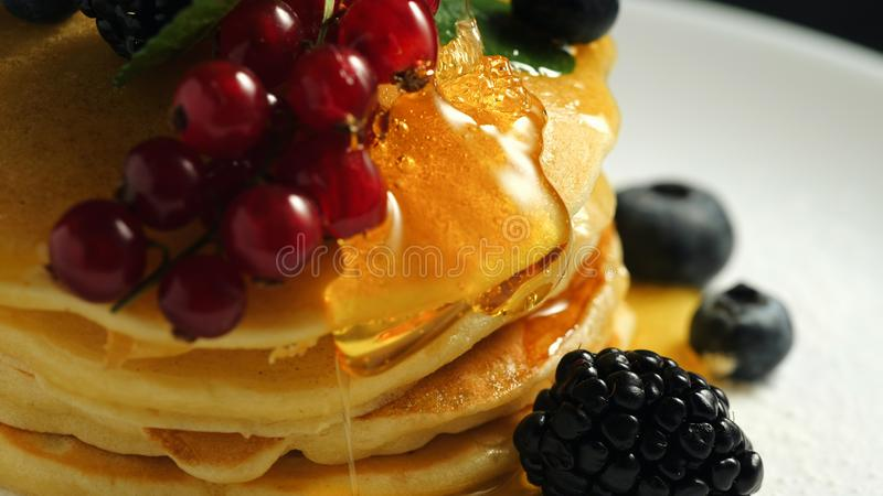 Stack of homemade pancakes or crepes decorated on top with forest berries - red currant, blackberry and blueberry. Delicious, healthy classic american royalty free stock images