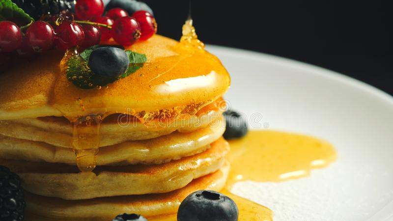 Stack of homemade pancakes or crepes decorated on top with forest berries - red currant, blackberry and blueberry stock images