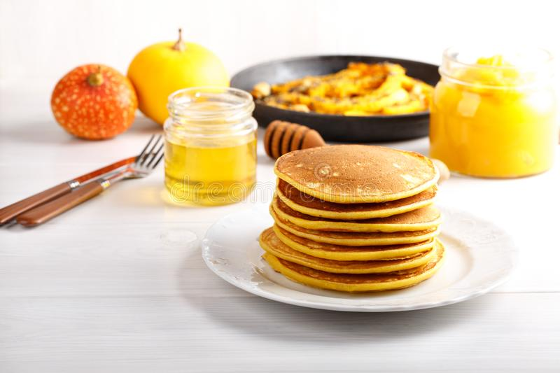 Stack of homemade pumpkin pancakes on white table stock photo