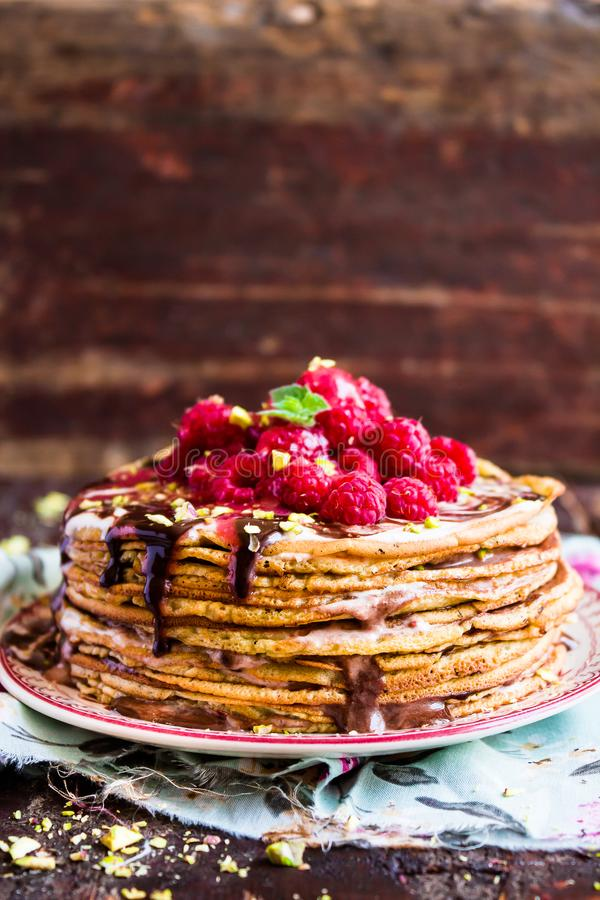 Stack of homemade thin pancakes or crepes or pancake cake with chocolate sauce, fresh raspberry, pistachios nuts decorated with fr stock photos