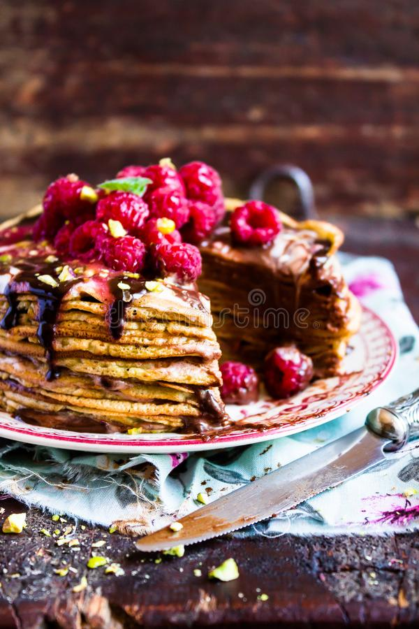 Stack of homemade thin pancakes or crepes or pancake cake with chocolate sauce, fresh raspberry, pistachios nuts decorated with fr. Esh mint leaves on a plate stock image