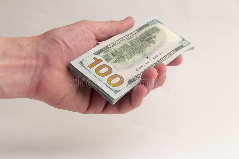 A stack of hundred-dollar bills in the left hand of a man. A person gives or takes an American thousand dollars. Bribe or salary. stock images