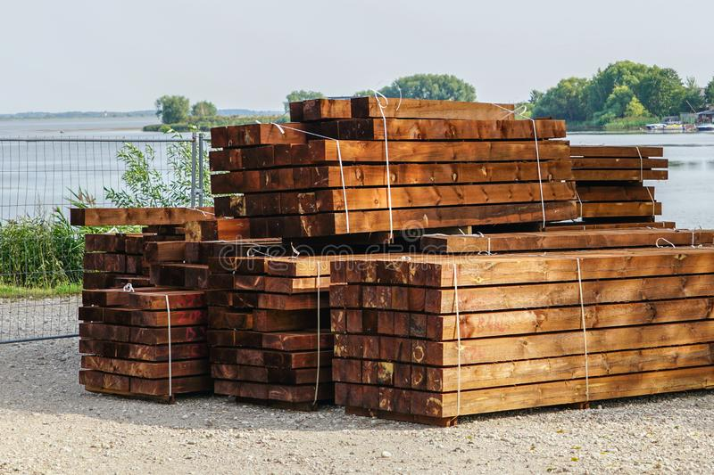 A stack of impregnated timber ready for the construction of a wooden house stock image