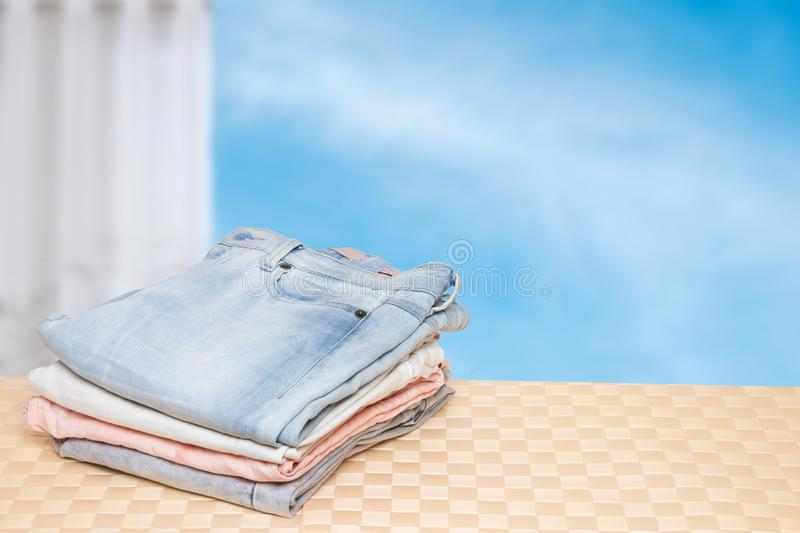 Stack of jeans. Closeup of a pile of colorful female denim pants on a bright table against abstract blurred cloudy sky. Space for. Your product display montage stock images