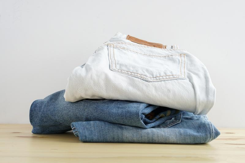 Stack of jeans in different colors on wooden table texture stock photo