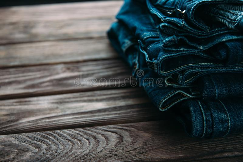 Stack of jeans pants on wooden table. Stack of blue jeans denim pants on a wooden table stock photo