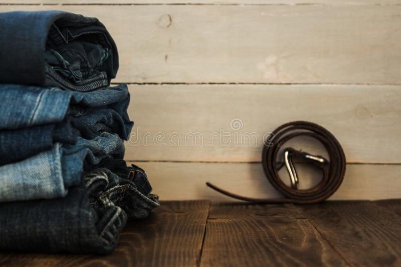 A stack of jeans on a wooden background and a belt royalty free stock photo