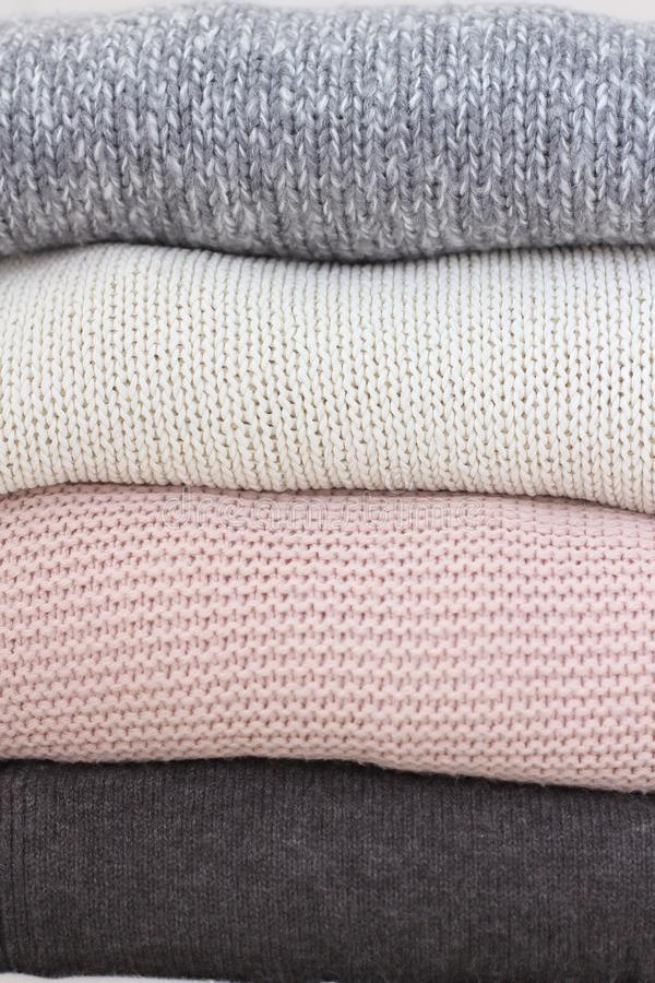 A stack of knitted sweaters background. Cozy warm, rustic-style hooded winter clothing. Stylish daily casual woolen autumn royalty free stock images