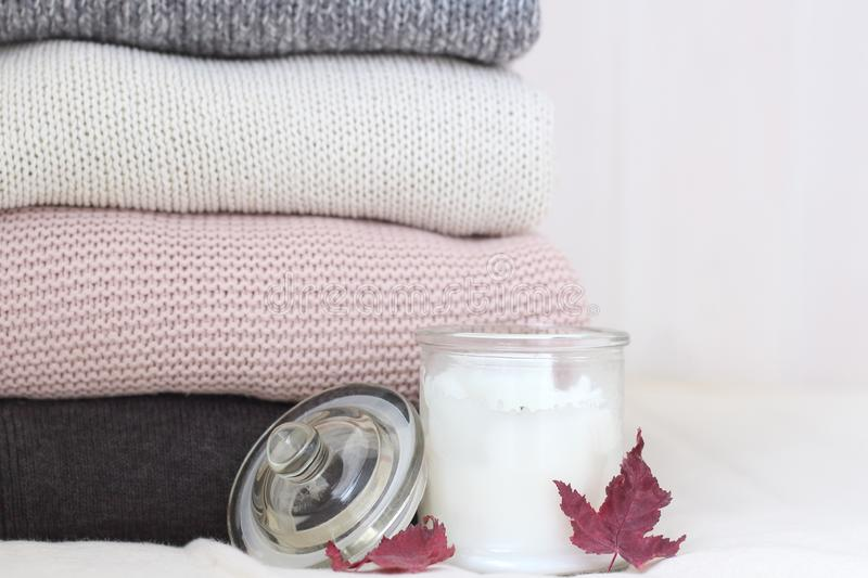 A stack of knitted sweaters on a linen pillow on a wooden wall background. Scented candle and fallen maple leaves. Cozy warm, royalty free stock photo