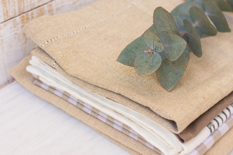 Stack of linen and cotton kitchen towels on white wood kitchen table, branch of silver dollar eucalyptus on top stock image