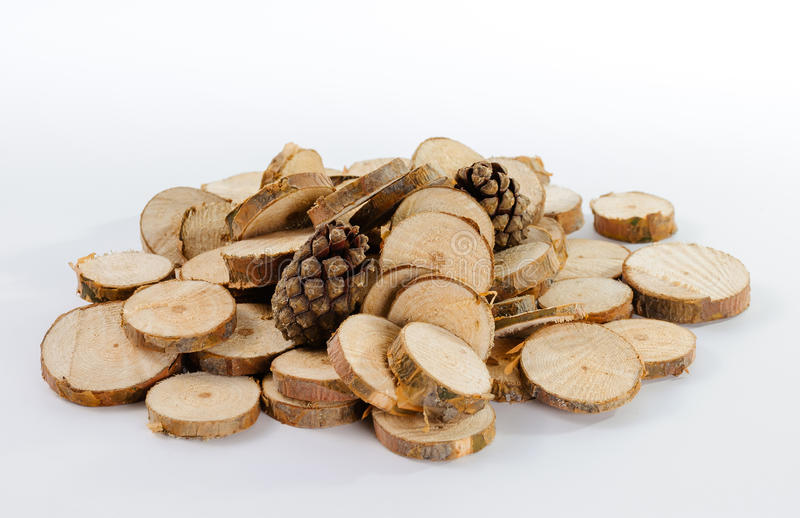 Stack of little round pieces of sawn pine branches and two pine. Cones on white background stock photo