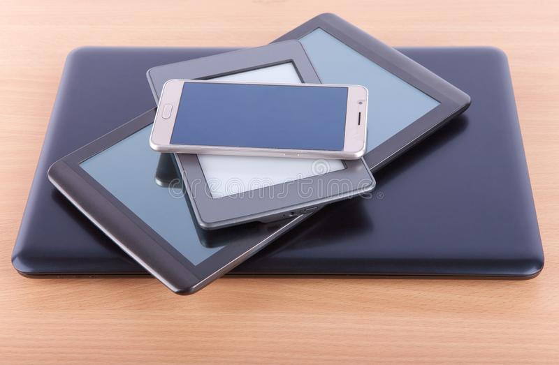 Stack made from notebook, tablet, ebook reader and a smatphone on a desk royalty free stock photos