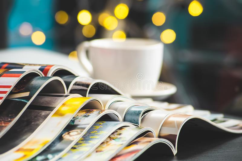Stack Magazines place or Old books on black desk with coffee cup background. selective focus royalty free stock image
