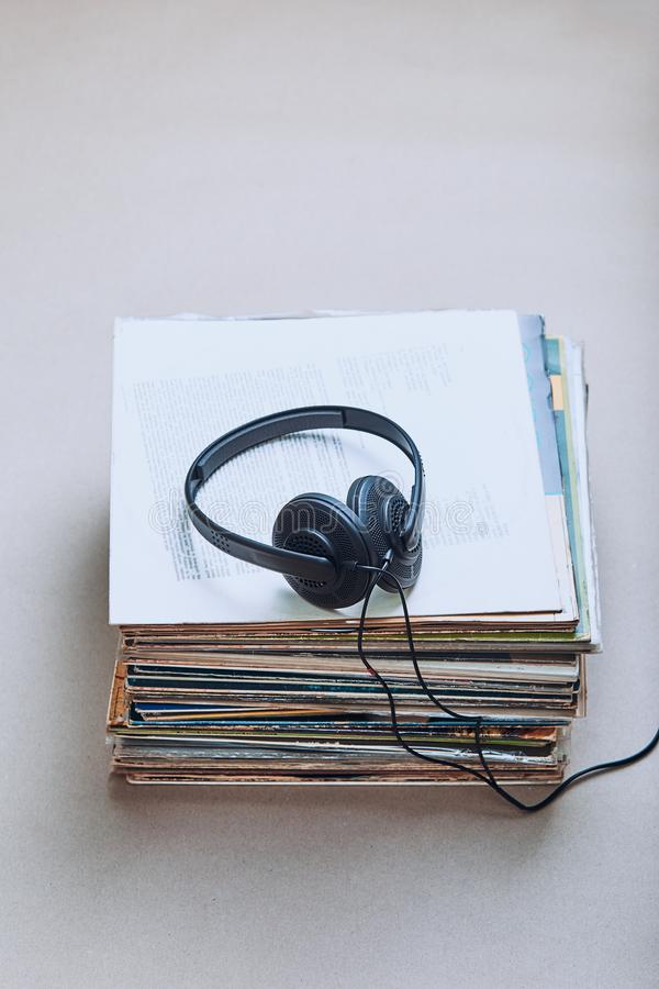 Stack of black vinyl records. Stack of many black vinyl records, headphones on the top of stack. Candid people, real moments, authentic situations stock image