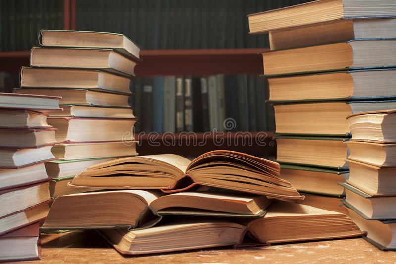 A stack of many old books on the table-background of bookshelve stock images