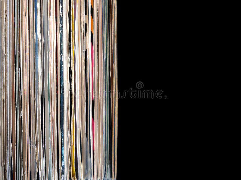 Stack of many vinyl records in old color covers on left side on photo on black background royalty free stock photography