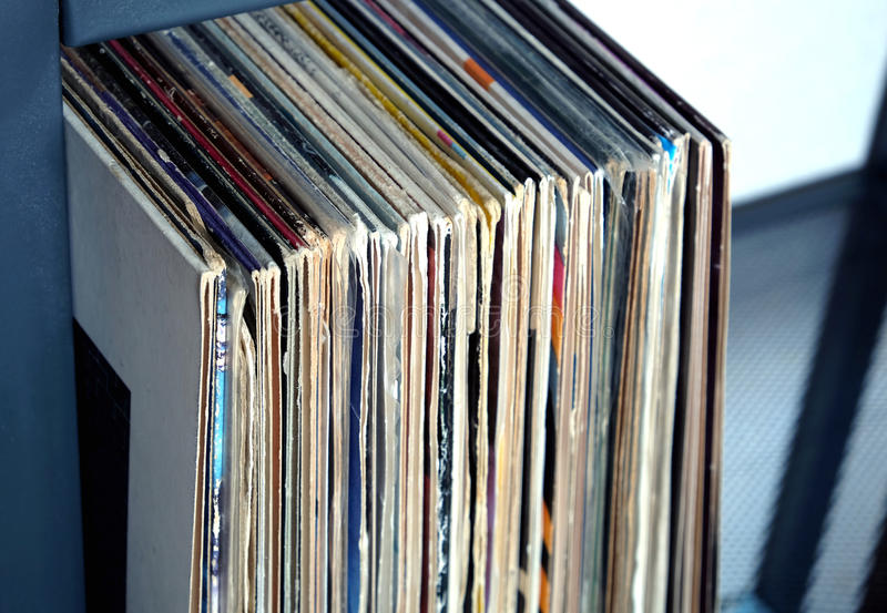Stack of many vinyl records in old color covers on a shelf side view. Pile of many close standing vinyl records in old color covers on a shelf side view closeup stock photo