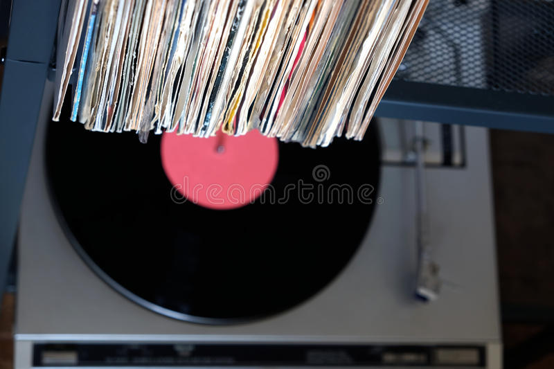 Stack of many vinyl records in old covers and turntable in gray case royalty free stock image
