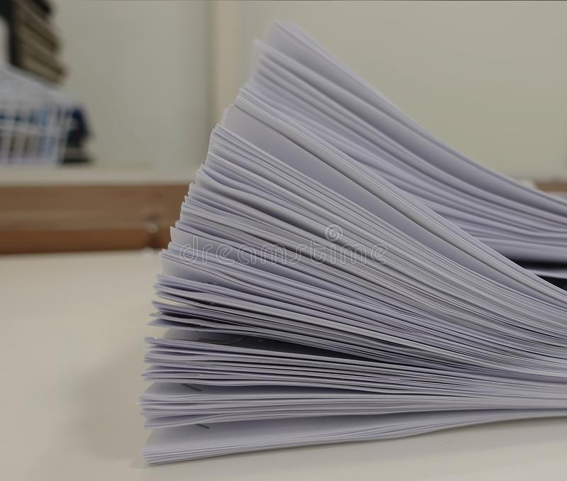 Stack of meeting paper on the table with blurred of office room stock images