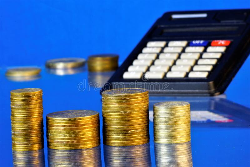 A stack of metal coins accountant and a calculator on a blue background. A coin is a monetary sign made of metal by means of coinage in the form of a regular stock image