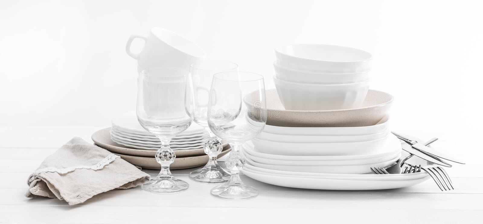 Stack of mixed white dishes and crystal glasses royalty free stock photo