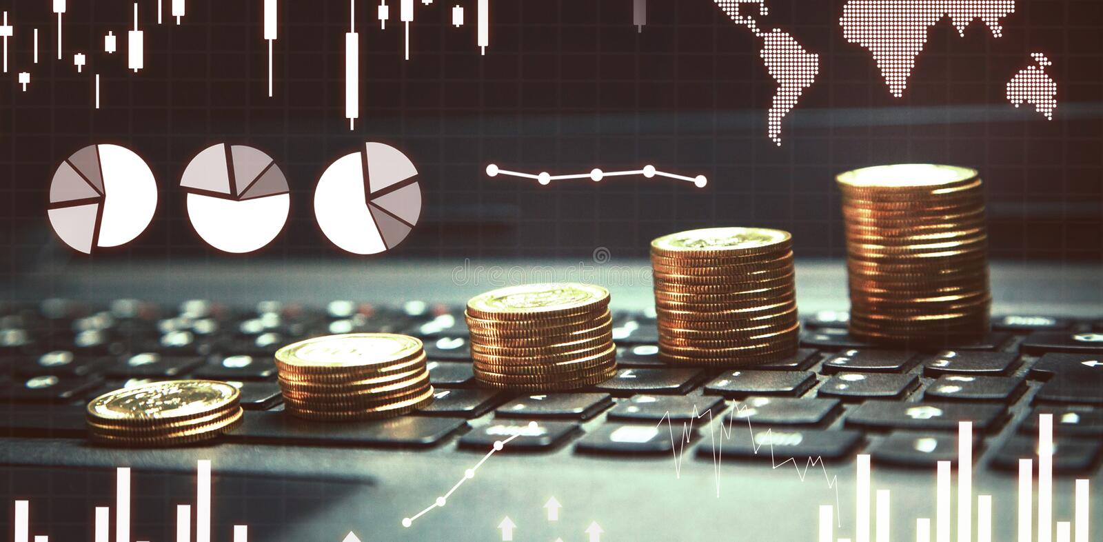 Stack of money coins on laptop keyboard with financial graphs royalty free stock photo