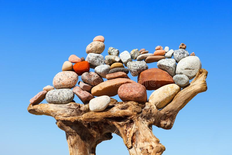 Stack of multicolored balanced stones on an old wooden snags, on a blue sky background. Concept of harmony and balance royalty free stock photo