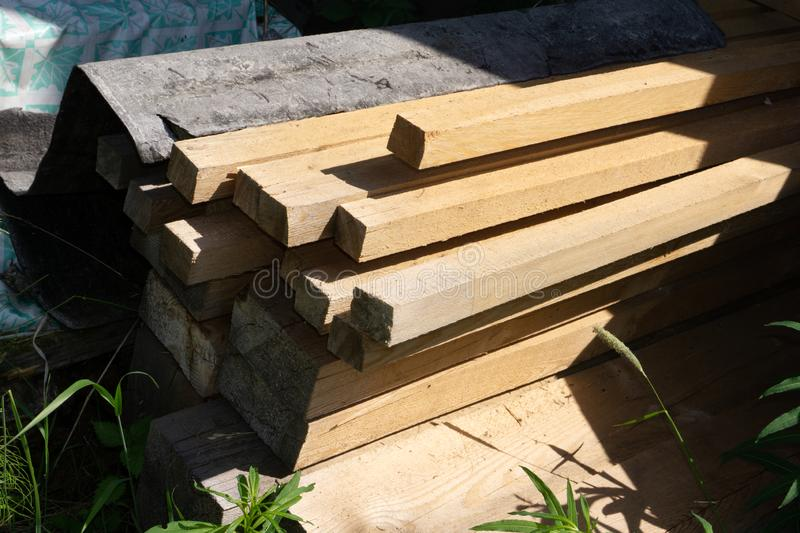 Stack of natural brown uneven rough wooden boards on building site. Industrial timber for carpentry, building, repairing and stock photography