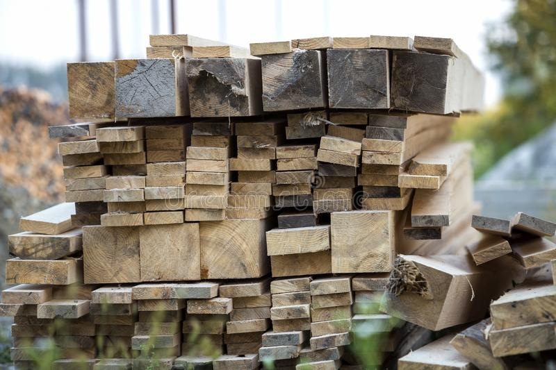 Stack of natural brown uneven rough wooden boards different size, cross-sectional view. Industrial timber for carpentry, building stock images