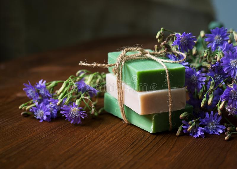 Stack of natural handmade soap among blue flowers on wooden background. Organic cosmetic products, low key, selective stock image