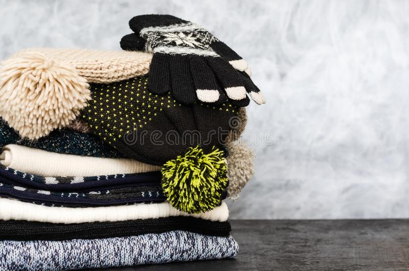 A stack of neatly folded knitted winter scarves, hats with pompons and gloves on gray background. Season of warm clothes stock photos